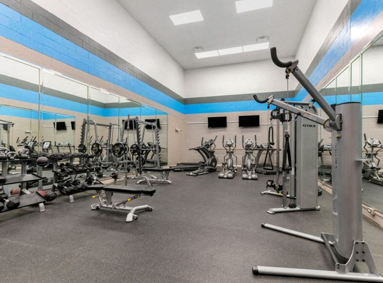 Bright Fitness Center with Exercise Equipment and Mirrored Walls